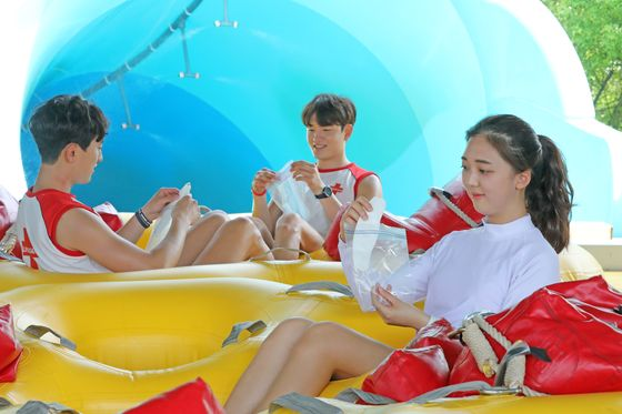 Employees working at Caribbean Bay, a water park located in Yongin, Gyeonggi, demonstrate how to store masks in complimentary plastic bags on June 4 prior to the park's official opening.  [NEWS1]
