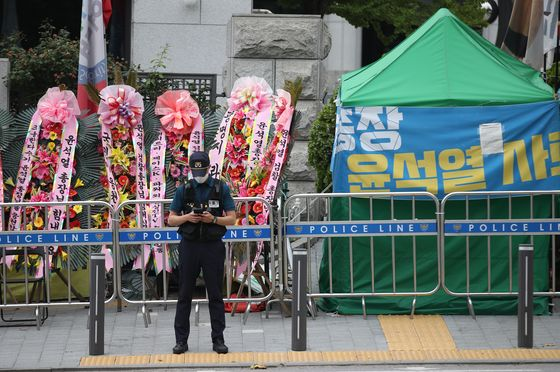 In front of the Supreme Prosecutors' Office building in Seocho-dong, Gangnam District of Seoul, flowers sent by the people to express their supports for Prosecutor General Yoon Seok-youl stand next to a protesters' tent demanding Yoon's resignation on June 29, 2020.  [YONHAP]