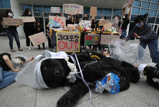 Activists hold a performance calling for an immediate ban on the repackaging of packaged products after a press conference in front of Emart's Seongsu branch in eastern Seoul on Thursday. Organized by nonprofit organizations including Green Korea and Green Future, the conference follows a government decision in late June to postpone a ban on retailers selling promotional repackaged bundles. [YONHAP]
