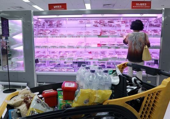 A shopper in front of the meat section at a discount mart in Seoul on Thursday. While the consumer price was flat in June, meat prices went up thanks to the emergency relief grant. Pork prices were up more than 16 percent while Korean beef went up 10 percent. [YONHAP]