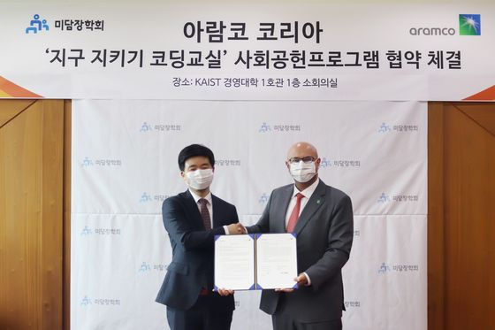 """Fahad A. Al-Sahali, head of Aramco Korea, right, and Jang Neung-in, Midam Scholarship Foundation's standing director, shake hands after signing a partnership agreement for 'Save Earth Coding School"""" program at KAIST College of Business in eastern Seoul."""