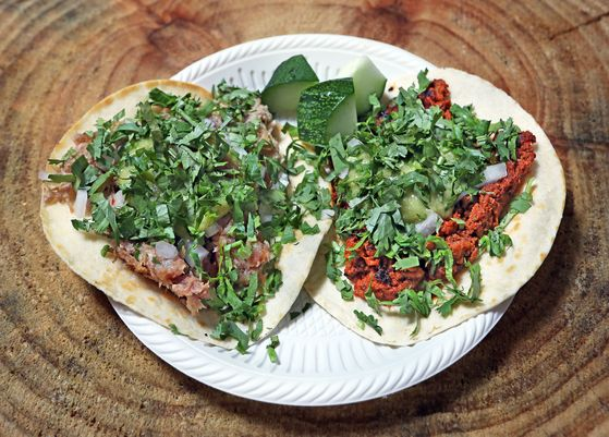 The two mainstays on the Taqueria Stan menu, pork shoulder, left, and chorizo, topped with diced white onions, salsa verde and cilantro. [PARK SANG-MOON]