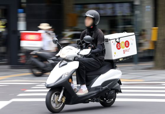 A food delivery in progress in Seoul on June 29. The coronavirus outbreak has driven a rise in online food delivery orders. [NEWS1]