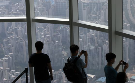 Visitors to Lotte World Tower in Songpa District, southern Seoul, look out at the view of apartment buildings. Songpa District is subject to tighter regulations that are likely to pass during the 21st National Assembly. [YONHAP]