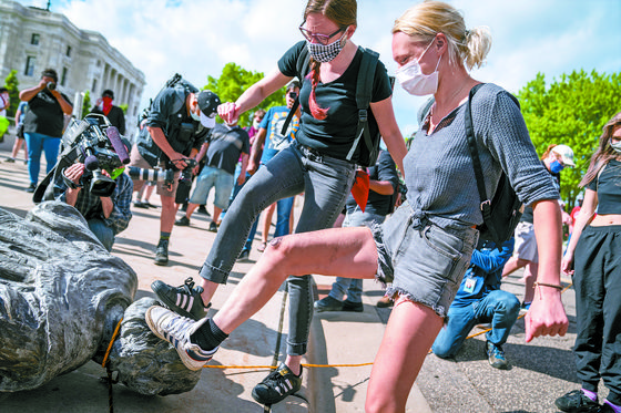 Americans stomp on a Christopher Columbus statue after it was toppled in front of the Minnesota State Capitol in St. Paul, June 10. [AP/YONHAP]