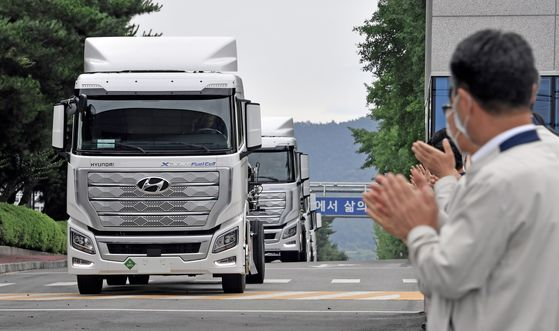Workers at Hyundai Motor's Jeonju plant in North Jeolla celebrate as the world's first mass-produced hydrogen-powered commercial vehicles, Xcient Fuel Cells, leave to be shipped to Switzerland. [HYUNDAI MOTOR]