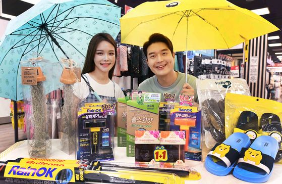 Models present rainy season equipment on sale at the Homeplus Gangseo District branch in western Seoul on Monday. Homeplus is offering discounts of up to 40 percent at nationwide offline stores and at its online mall for products including automobile supplies, drying racks, umbrellas, household appliances and items for the upcoming rainy season until July 15. [YONHAP]