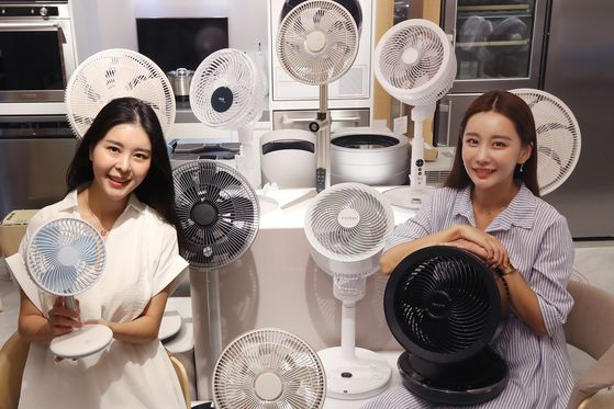 Models show off fans at the Lotte Department Store branch in Jung District, central Seoul, on Monday. As the country faces a heat wave, the department store is selling various types of popular fans at discounted prices. [YONHAP]
