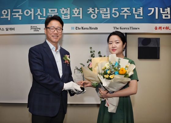 Ryu Kwon-ha, left, CEO of the Korea JoongAng Daily, and Yoon So-yeon, right, a culture reporter at the Korea JoongAng Daily, pose for a photo after the Foreign Language Newspapers Association of Korea selected Yoon as one of five outstanding reporters of the year during the event celebrating the fifth anniversary of the association on Monday. Yoon was credited with writing stories, creating video news clips on K-pop and providing prompt news on Korean pop culture.  [PARK SANG-MOON]