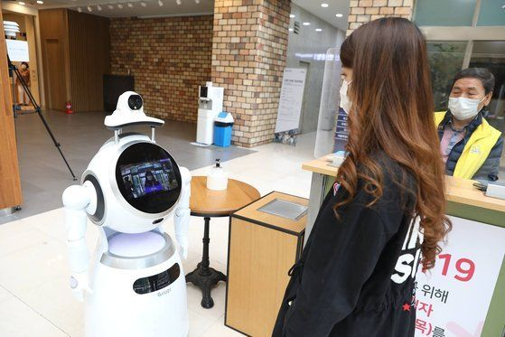 Woody takes a student's temperatures and checks if she is wearing her mask properly. Seocho District, southern Seoul, is planning to install infrared cameras and robots with built-in facial recognition functions at 51 schools by the end of July. [SEOCHO DISTRICT OFFICE]