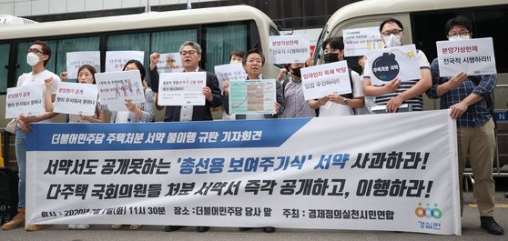 The Citizens' Coalition for Economic Justice holds a press conference on Tuesday in front of the Democratic Party's headquarters building in Yeouido, Seoul, to urge its lawmakers to keep a campaign promise to sell their second homes.  [YONHAP]