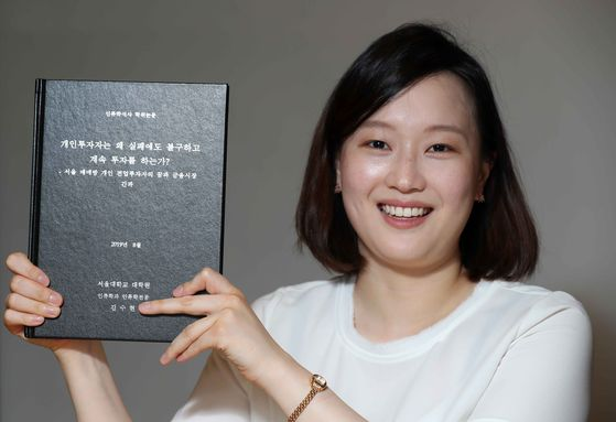 Kim Soo-hyeon, 26, a graduate student of Seoul National University, holds up her thesis at an interview with the JoongAng Ilbo. [KIM SANG-SEON]