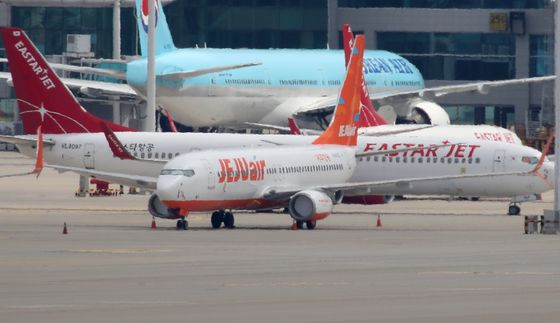 Jeju Air passenger aircraft parked at Incheon International Airport on Tuesday. Jeju Air on Tuesday denied Eastar Jet's claims that it was behind the restructuring of Eastar Jet. [YONHAP]