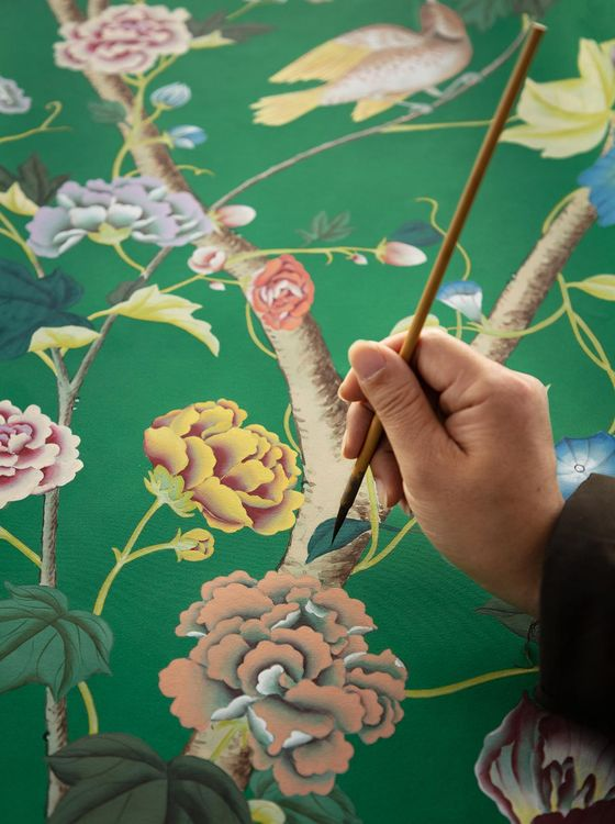 A craftsman hand paints de Gournay's wallpaper. [DE GOURNAY]