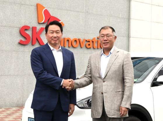 SK Group Chairman Chey Tae-won, left, and Hyundai Motor Group Executive Vice Chairman Euisun Chung shake hands at SK Innovation's battery factory in Seosan, South Chungcheong, on Tuesday. [SK GROUP]