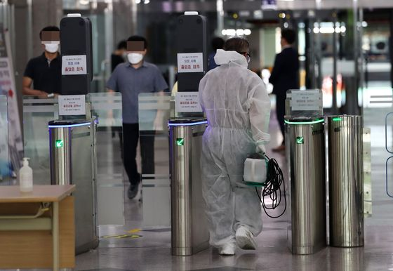 A quarantine official arrives at a government buildng in Daejeon on Monday after an official tested positive on Wednesday. [YONHAP]