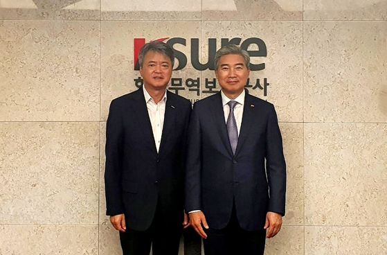 From left, Korea Trade Insurance Corp. Chairman Lee In-ho and Korea Importers Association Chairman Hong Kwang-hee at the state-owned institution's office in Seoul on Wednesday. [Koima]