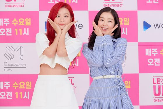 "Irene, right, and Seulgi of Red Velvet pose for photos during an online press conference held on Thursday afternoon for the new online reality series ""Level Up Project."" [SM C&C]"