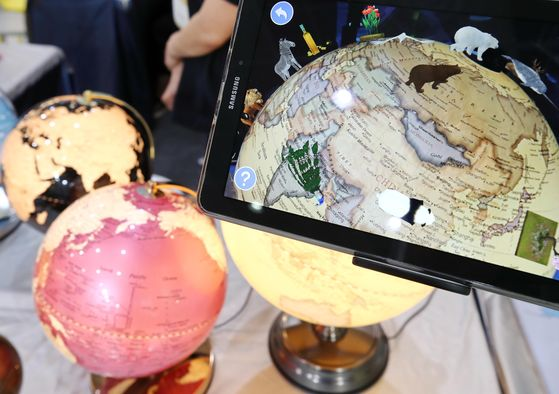 Augmented reality globes are displayed inside a booth at Seoul International Young Children Education & KidsFair held in Coex in southern Seoul on Thursday afternoon. The fair will run through Sunday. [YONHAP]