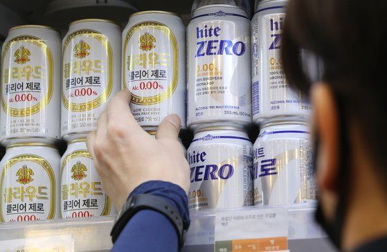 A man picks up a can of Kloud Clear Zero, a nonalcoholic beer from Lotte Chilsung Beverage, at a supermarket in Seoul. [YONHAP]