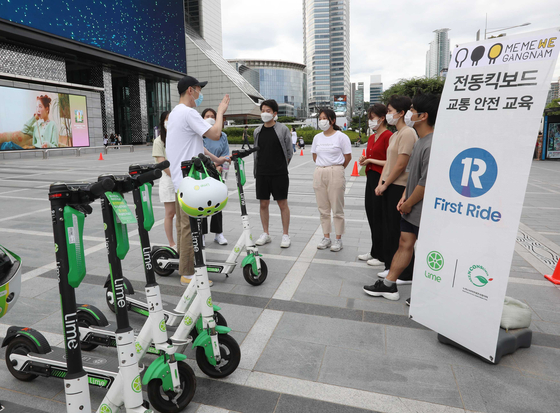 Employees from scooter-sharing service Lime teach people how to correctly park electric scooters at Coex in Gangnam District, southern Seoul, Sunday. [LIME KOREA]