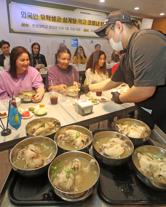 International students try samgyetang, a traditional chicken soup with ginseng, at an event to celebrate Chobok, the first day of the year's hottest season according to the Korean calendar, at Hansung University in Seongbuk District, central Seoul, on Monday. Samgyetang is commonly eaten by Koreans to beat the heat. This year, Chobok falls on Thursday. [YONHAP]
