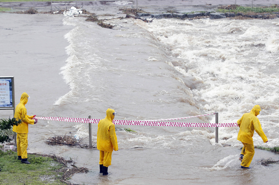 Local government officials set cordon off an area in Gwangju, on Monday, as a stream floods after heavy rainfall. About 200 millimeters of rain pounded South Korea's southern regions on Monday, leaving several people dead and causing traffic accidents, flooding and the destruction of roads, houses and facilities. [NEWS1]