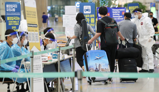 Health officials instruct international arrivals on their transportation options at Incheon International Airport, South Korea's main gateway west of Seoul, on Sunday. The country began on July 13 to require arrivals from high-risk nations to hand in a certificate showing they tested negative for Covid-19. [YONHAP]