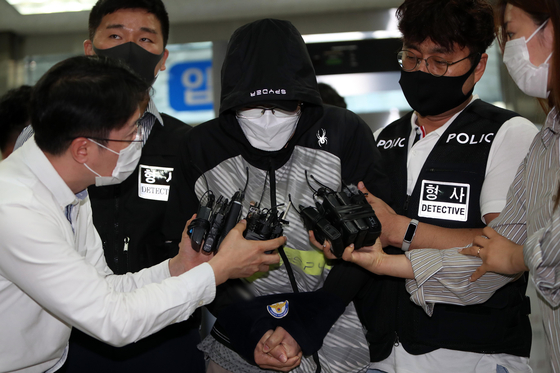 Ahn Joo-hyeon, the so-called team doctor accused of abusing current and former triathletes, is surrounded by reporters as he makes his first public appearance since the death of Choi Suk-hyeong at a Daegu district court Monday afternoon. An arrest warrant was issued by the court later that day. [YONHAP]