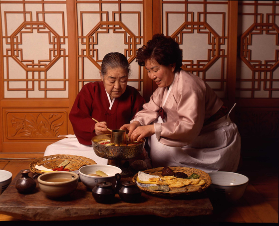 Hwang's oldest daughter Han bok-ryeo, right, is following in the footsteps of her mother. [KOREAN ROYAL CUISINE CULTURE FOUNDATION]