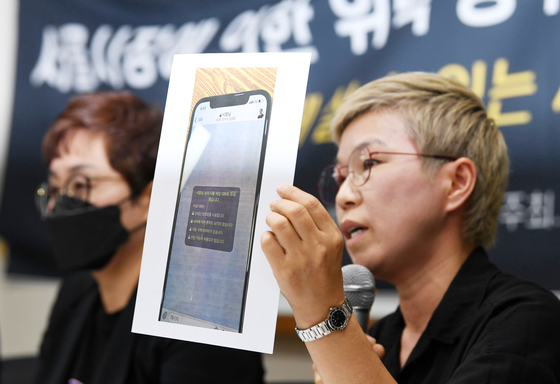 Kim Jae-ryon, right, a lawyer for former secretary of deceased Seoul Mayor Park Won-soon, speaks during a press conference on the late mayor's alleged sexual misconduct Monday. Kim showed a photo of a text message Park allegedly sent to the victim.  [YONHAP]