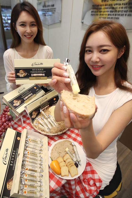 Models pose with high-end French butter La Conviette, also dubbed the Hermes of butter, at Shinsegae Department Store in central Seoul on Tuesday. Until recently, consumers in Korea were only able to purchase the butter from overseas. [YONHAP]