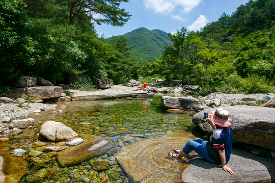 Visitors to Gallon Valley in Goesan County, North Chungcheon, take a rest. [LIETTO]