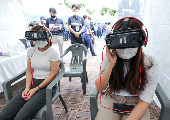 Participants experience virtual job interviews using VR goggles at a job fair held in Nowon District, northern Seoul, Wednesday. The Nowon District office organized the event to provide job consulting and employment opportunities to those struggling to find jobs due to the coronavirus pandemic. A total of 57 companies participated and are expected to hire around 275 people from the event. [YONHAP]