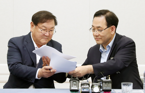Democratic Party (DP) Rep. Kim Tae-nyeon, left, and United Future Party (UFP) Rep. Joo Ho-young exchange signed agreements on Tuesday.  [YONHAP]