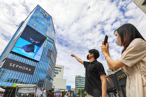 Passersby take photos of a media art piece showcased via a digital sign on an outer wall of the Hyundai U-Plex Department Store in Sinchon, western Seoul, on Wednesday morning. [YONHAP]