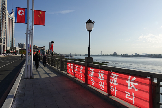 North Korean and Chinese flags decorate the streets of Dandong, China, in October last year, as the two countries celebrated their 70th anniversary of bilateral relations. [YONHAP]