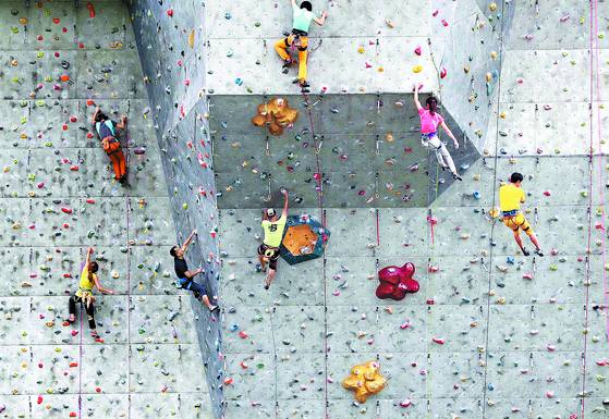 Sports climbers enjoy indoor climbing at an artificial rock wall in Nowon District, northern Seoul, on Wednesday. [KIM SANG-SEON]