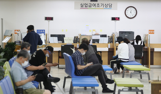 People wait to apply for unemployment benefits at a center in Jung District, central Seoul, on Monday. [YONHAP]