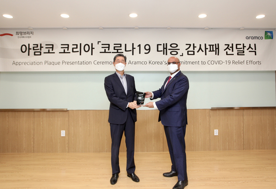 Aramco Korea's Representative Director Fahad A. Al-Sahali, right, and Hope Bridge's Chairperson Song Pil-ho pose at a ceremony ceremony held at Hope Bridge's headquarters in western Seoul, Wednesday. [ARAMCO KOREA]