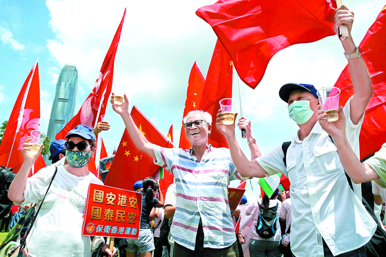 Pro-China supporters hold Chinese national flags during a rally to celebrate the approval of a national security law for Hong Kong, in Hong Kong, Tuesday, June 30, 2020 [AP/YONHAP]