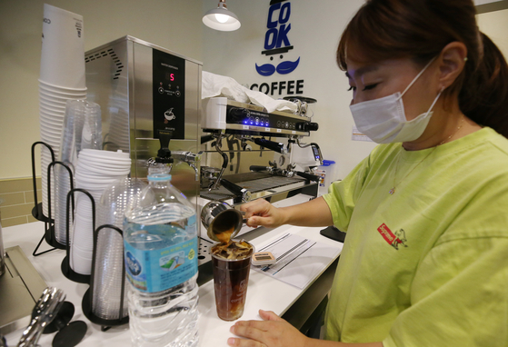 An employee at a coffee shop in Seo District, Incheon, on Thursday uses bottled water to make an Americano. The city is struggling to deal with larvae contamination in the water supply, a year after tap water was tainted due to mishandling at a treatment facility in June last year. [YONHAP]