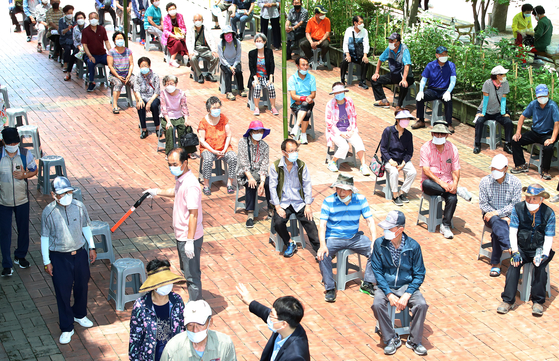 Senior citizens exercise social distancing while waiting in line to receive gift sets containing ginseng chicken soup and fruit. The handouts were provided at a welfare center for seniors in Dalseo District, Daegu, on Thursday. [NEWS1]