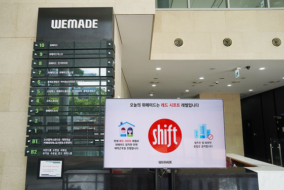 A panel at WeMade's headquarters in Pangyo, Gyeonggi, shows the Shift level. Red means the danger of infection is high and therefore all employees should stay home. [WEMADE]