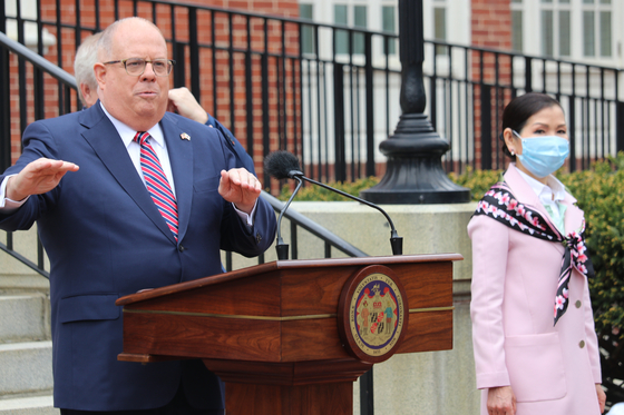 Maryland Gov. Larry Hogan, speaking at a news conference on April 20, announces that the state had received 500,000 Covid-19 test kits from South Korea with the help of his wife, Yumi Hogan, right. [AP/YONHAP]