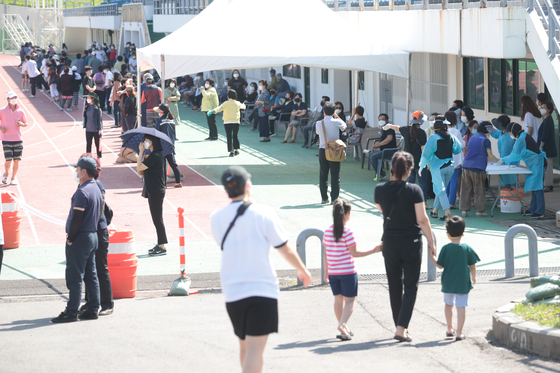 Hundreds of people line up to get tested for Covid-19 at a gymnasium in Hallim-eup in Jeju City Friday after a Seoul women tested positive after traveling to the island earlier this month. So far, four people linked to this woman have been infected with the virus. [YONHAP]