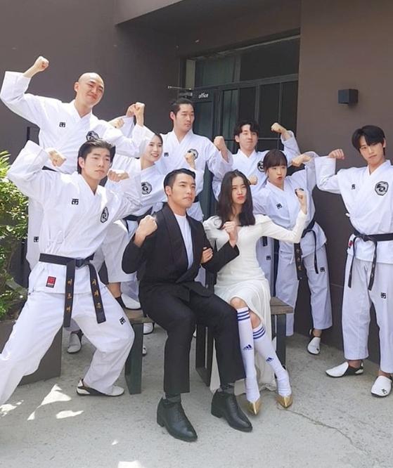 Celebrity couple Woo Hye-rim and Shin Min-cheol, center, take a wedding photograph with members of Shin's extreme taekwondo group Mirme. [RRR ENTERTAINMENT]