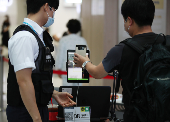 A visitor scans a QR code with his mobile phone Sunday to enter Seoul National University Hospital in Jongno District, central Seoul. The hospital is now requiring all visitors to use a digitalized entry log system to keep track of possible coronavirus infections. [YONHAP]