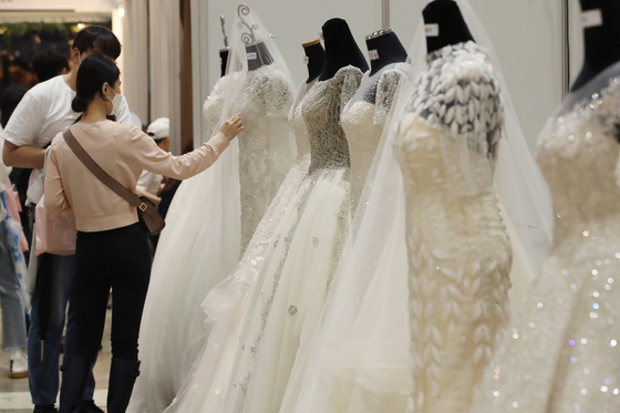 A couple looks at a wedding dress at Coex Mall in Samseong-dong, southern Seoul, on Sunday. The 54th edition of the two-day wedding fair was hosted by Weddex Wedding, a wedding consulting firm. [YONHAP]