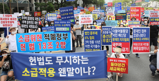 Protests over the government's real estate measures are held in front of the Korea Deposit Insurance Corporation on Saturday in downtown Seoul, as a public backlash grows over the government's regulations on higher property and capital gains taxes. [YONHAP]
